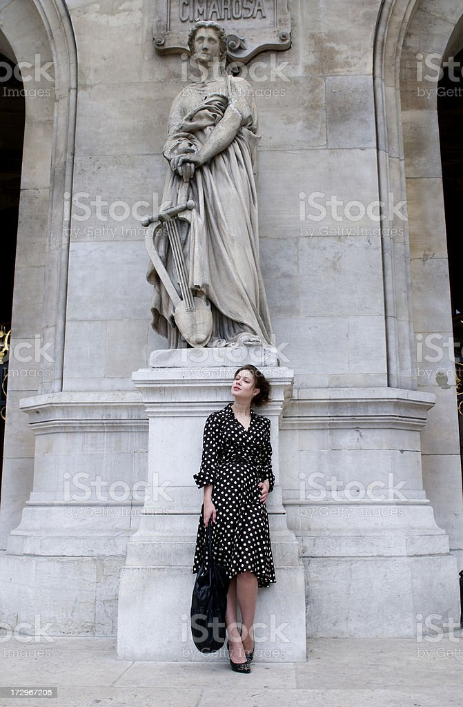 young woman leaning agaist statue enjoying the moment royalty-free stock photo