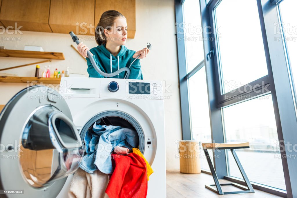 young woman leaning at broken washing machine stock photo