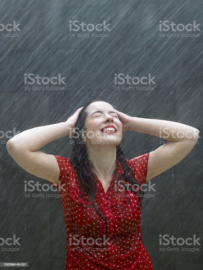 Young woman leaning back in rain, hands on head, eyes closed royalty-free stock photo
