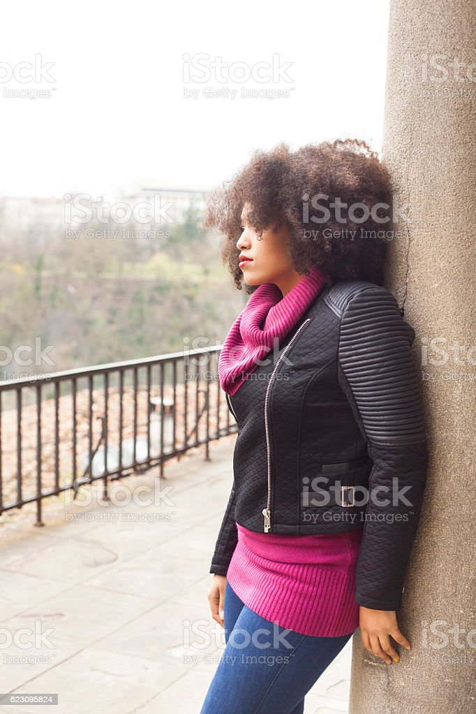 Young woman leaning back on column stock photo