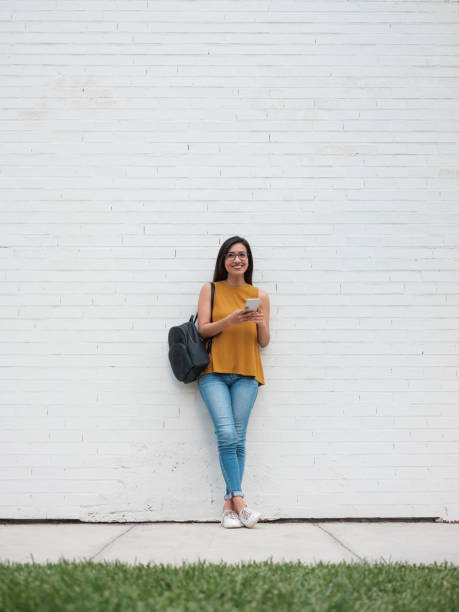 Young woman leaning on a wall smiling at the camera stock photo