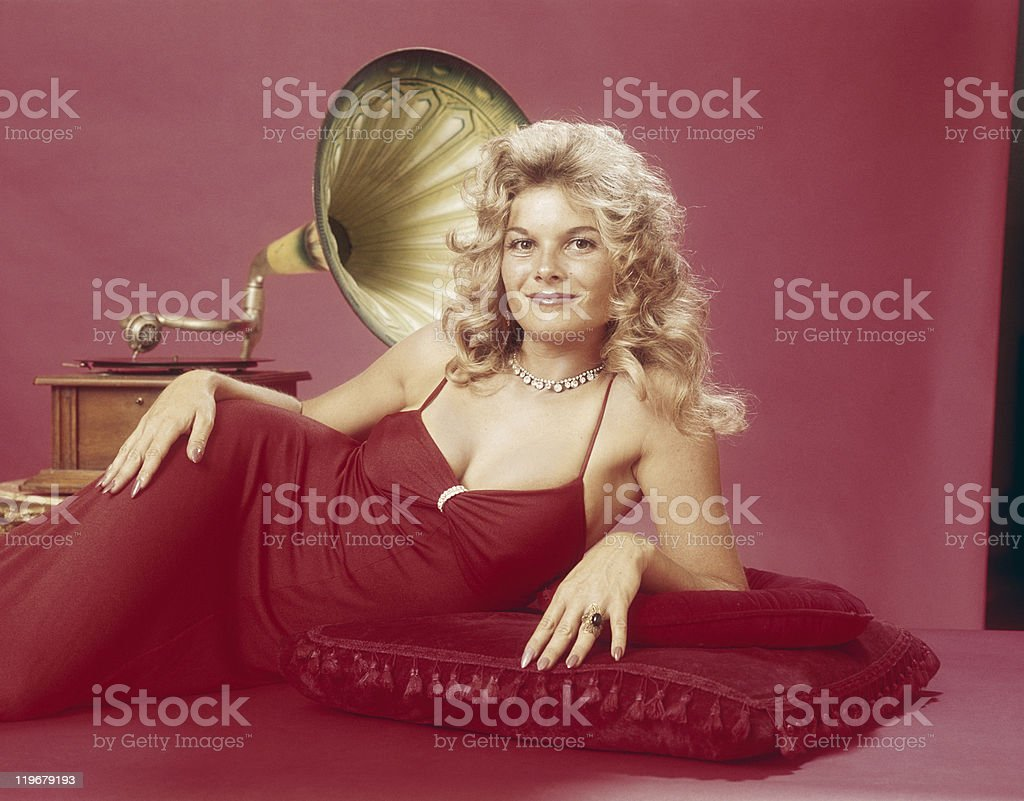 Young woman leaning on cushion with gramophone in background, smiling, portrait stock photo