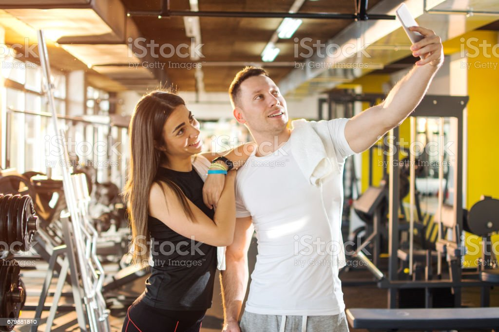 Young woman leaning on her boyfriend's shoulder while taking a selfie in gym. - foto de acervo