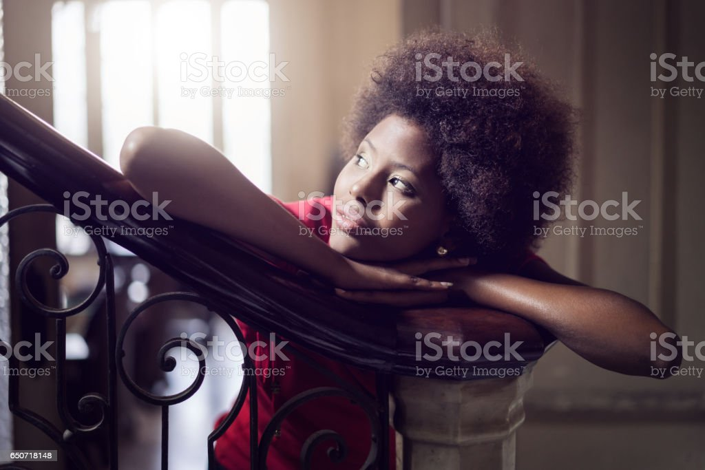 young woman leaning on newel post at home stock photo
