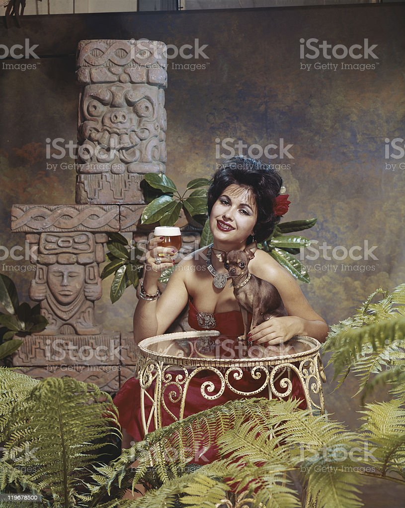 Young woman leaning on table with chihuahua  stock photo