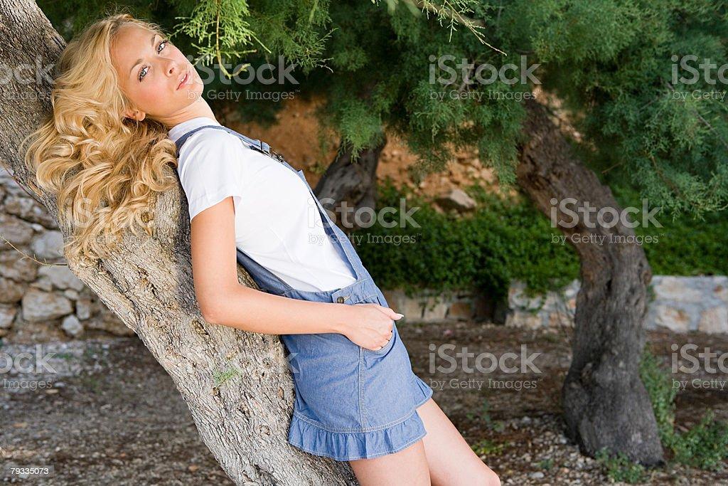 Junge Frau schiefen auf Baum Lizenzfreies stock-foto
