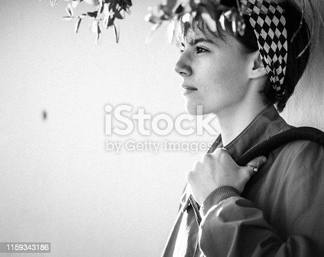 Young woman leaning on white wall in B&W
