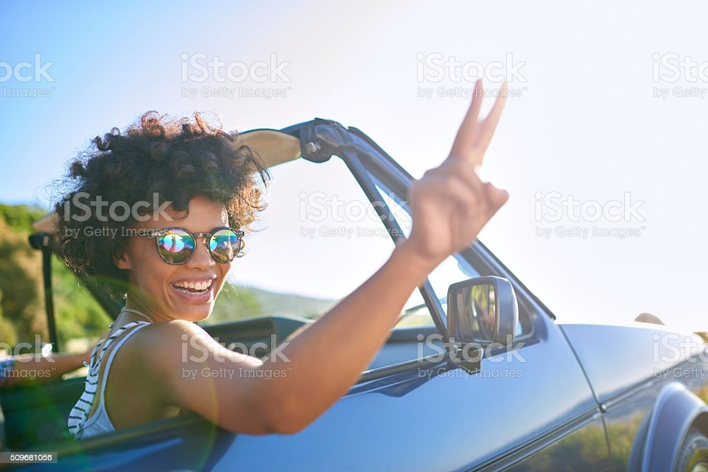 Young woman leaning out the window of car stock photo