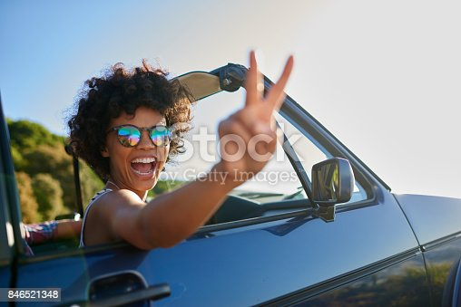 istock Young woman leaning out the window of car 846521348