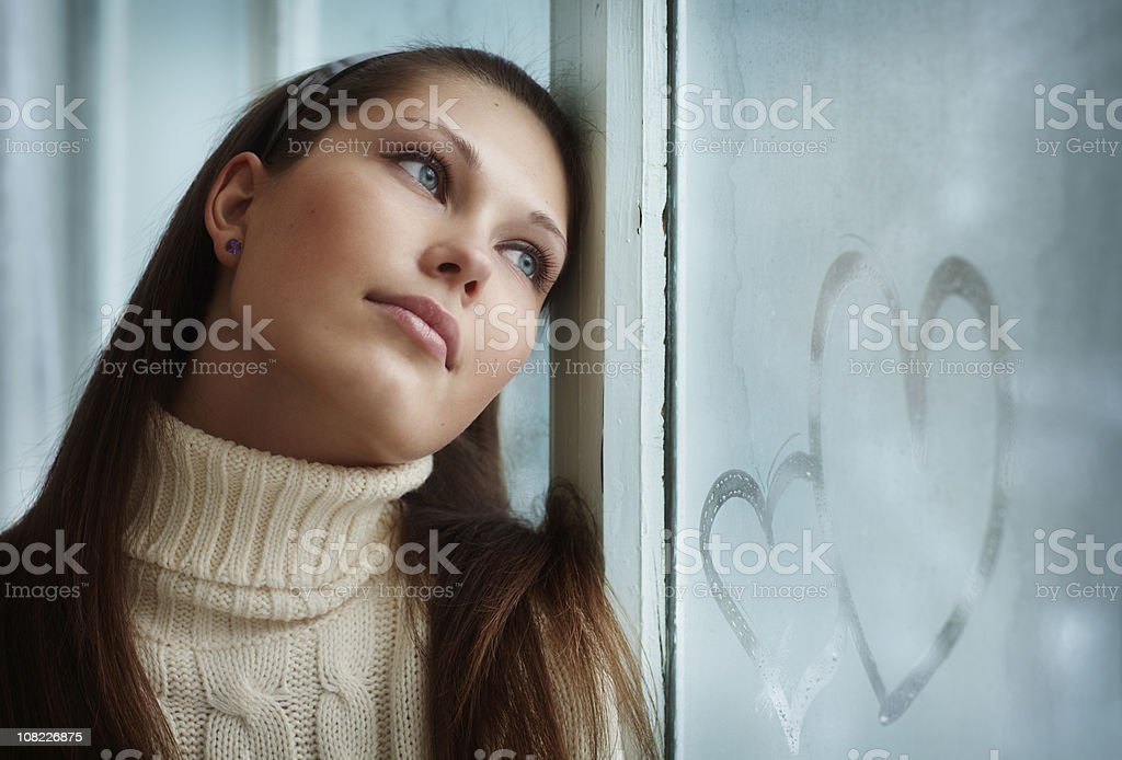 Young Woman Leans Against Window with Hearts Drawn in Frost royalty-free stock photo