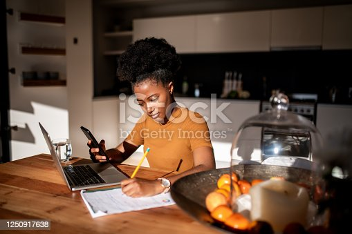 Young woman learning online with laptop and phone, she is taking notes in a notebook