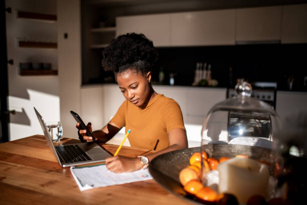 Young woman learning online with laptop and phone, she is taking notes in a notebook stock photo