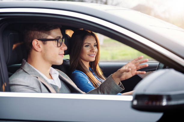 Young woman learning to drive Teenager or young woman learning to drive a car with driving instructor. Woman is confident and she is driving like a pro. driving instructor stock pictures, royalty-free photos & images