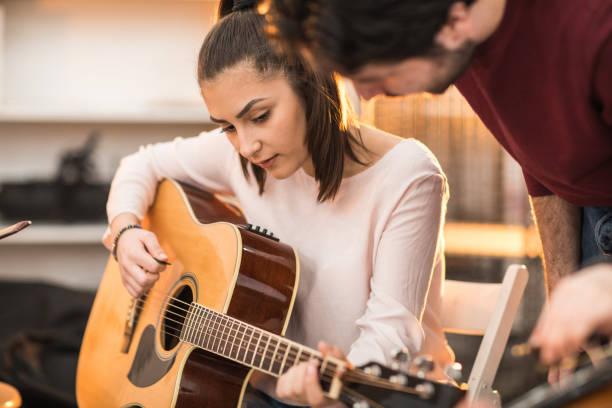 junge frau, die lernen, gitarre zu spielen - motivationsmusik stock-fotos und bilder