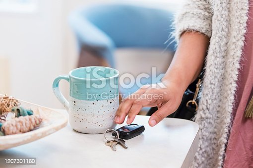 Cropped view of a young woman leaving home in the morning, grabbing her car keys off the kitchen counter.
