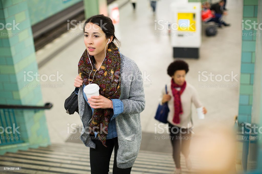 Young woman leaving subway station stock photo
