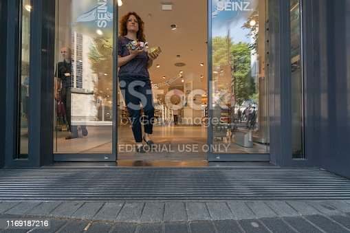 Cologne, Germany -  June 25, 2019: Photography of young woman leaving the food store with food and drink in the hands in the summer hot day.  Theme of heat touristic time in the city.