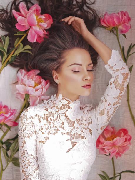 Young woman lies among peonies stock photo