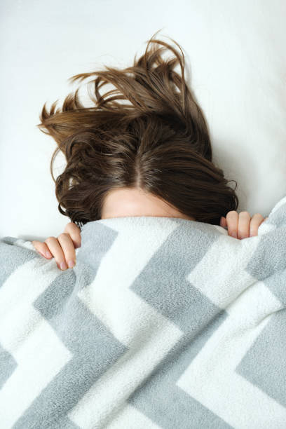 A young woman lies in bed under a blanket and have a hard time waking up in the morning stock photo