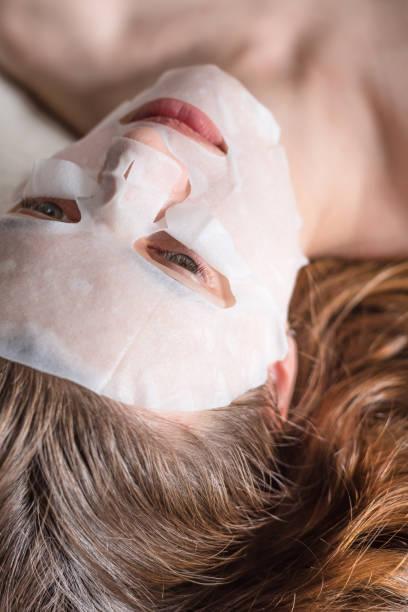 Uma jovem mulher encontra-se com uma máscara de folha plástica sobre um fundo escuro - o conceito de close-up facial, - foto de acervo