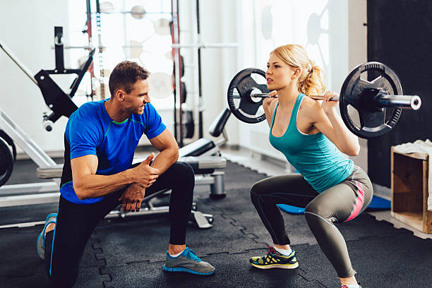 young woman lifting barbell with her personal trainer assistance. - entrenador personal fotografías e imágenes de stock