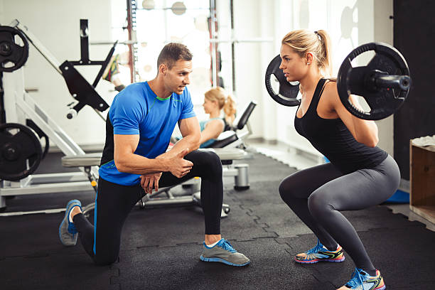 Young woman lifting barbell with her personal trainer motivation. stock photo