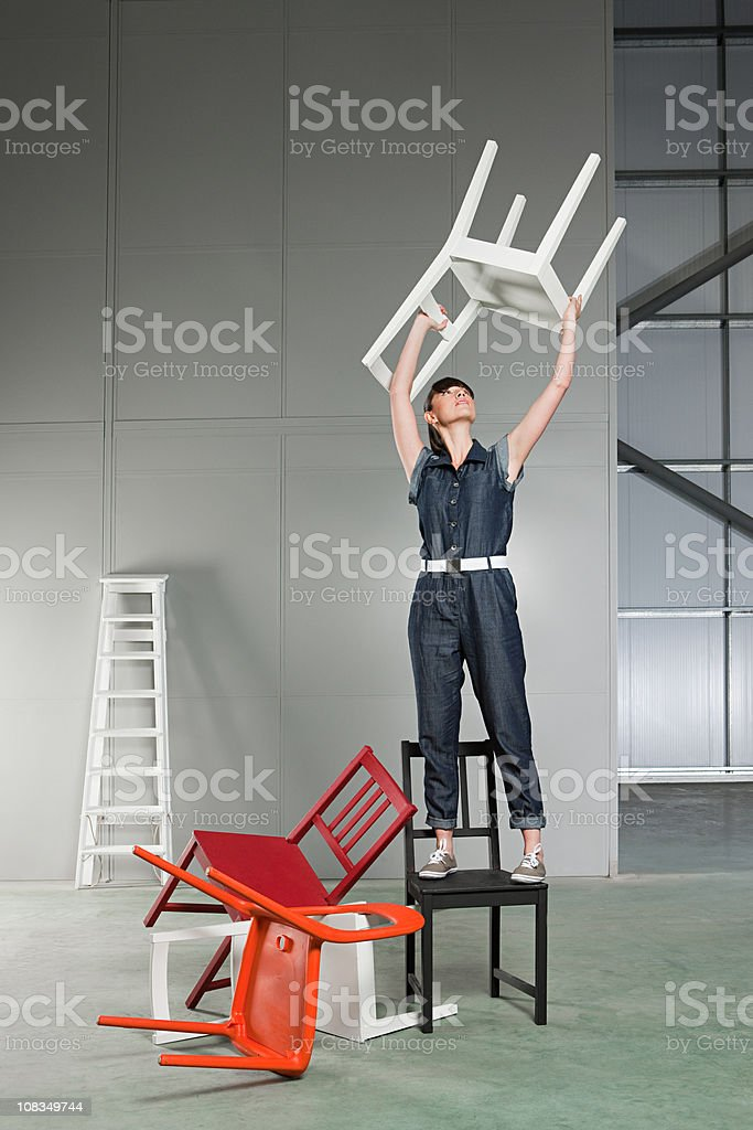 Young woman lifting chair above her head stock photo