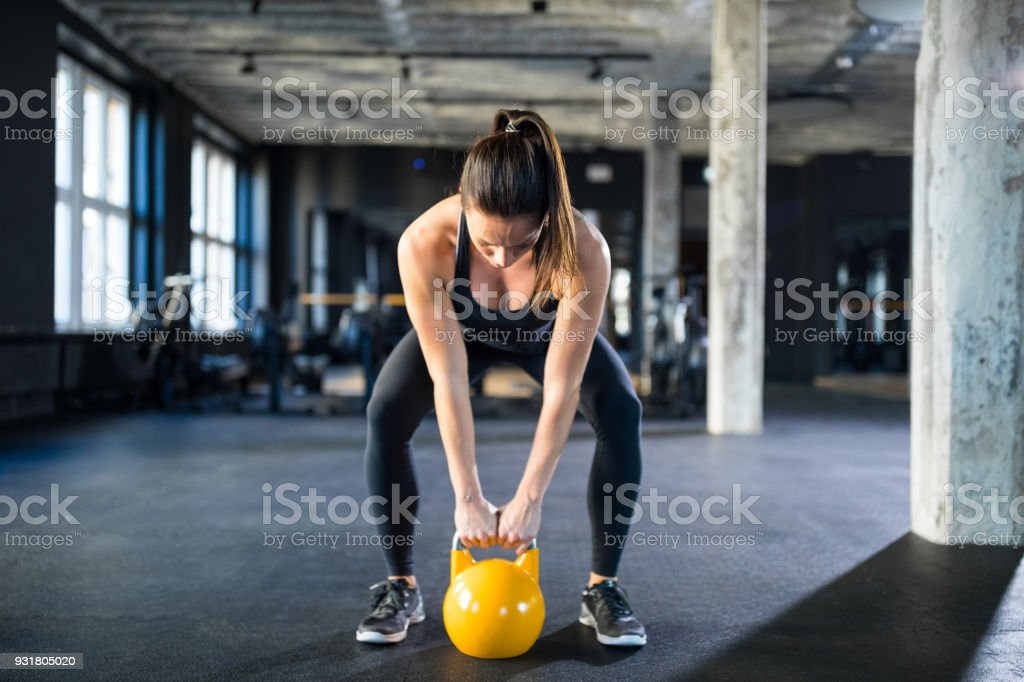 Young woman lifting kettlebell in gym stock photo