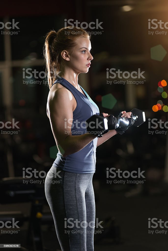 Young woman lifting the dumbbells royalty-free stock photo