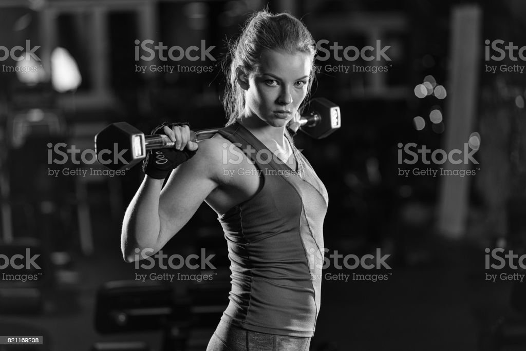 Young woman lifting the dumbbells stock photo