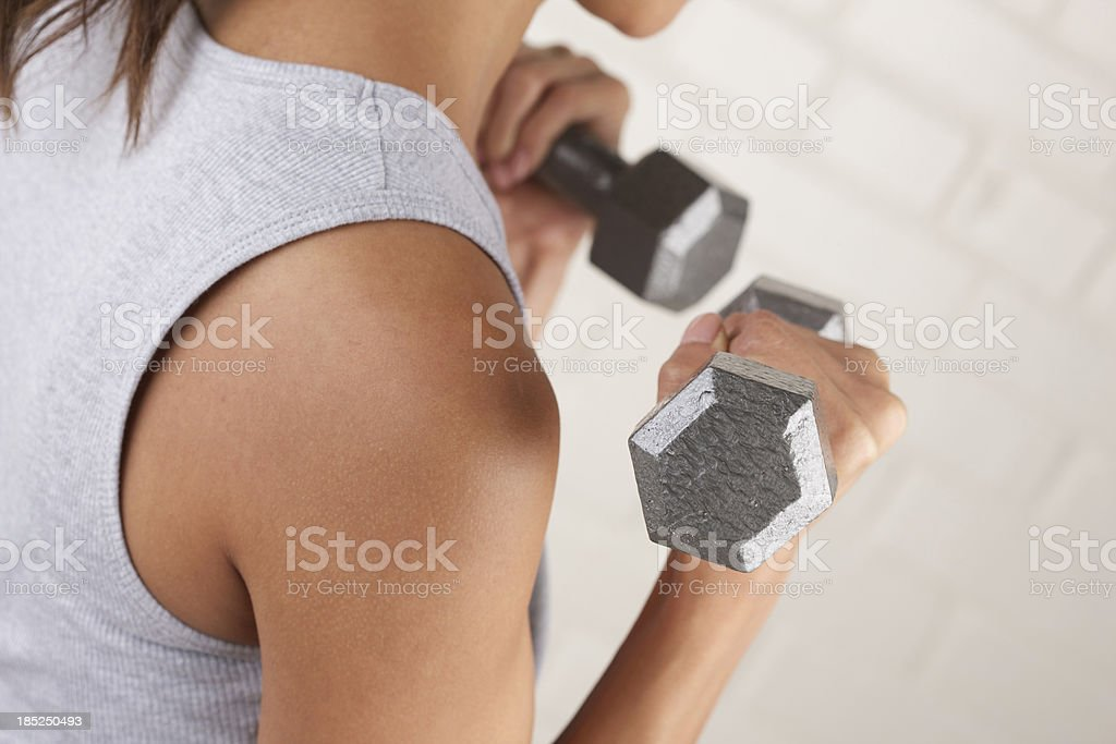 Young woman lifting two metal dumbbells royalty-free stock photo