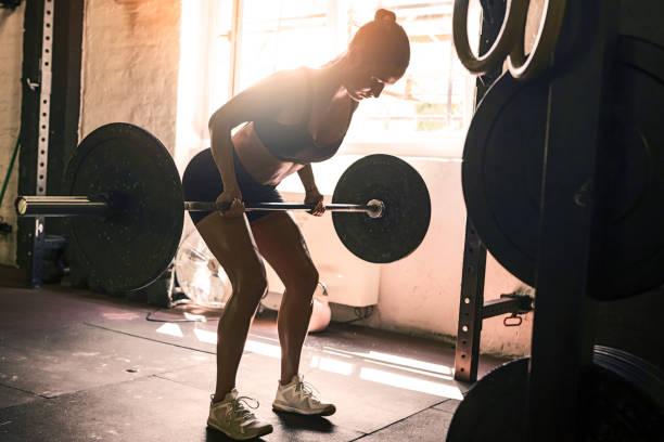 Junge Frau, die Gewichte hebt – Foto