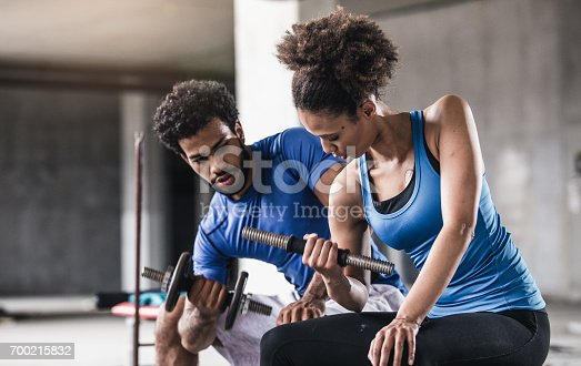 istock Young Woman Lifting Weights With Personal Coach Beside Her 700215832
