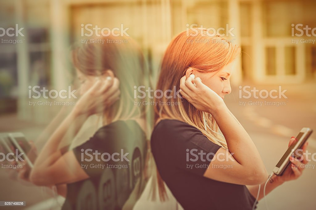 Young woman listen to music by smartphone stock photo
