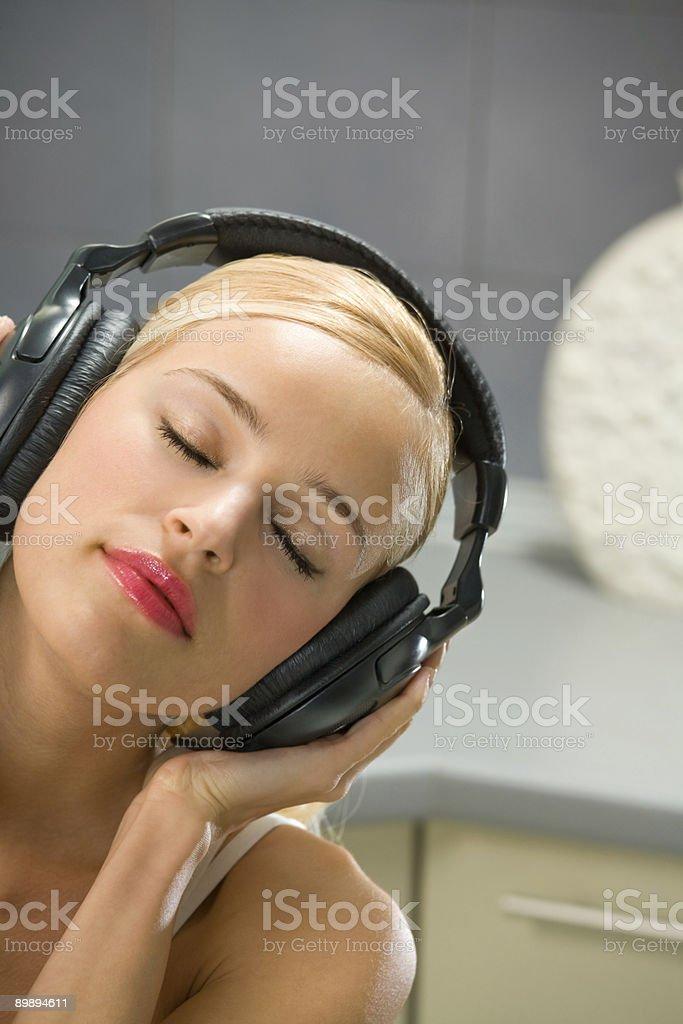 Junge Frau hört Musik im Kopfhörer wie zu Hause fühlen. Lizenzfreies stock-foto