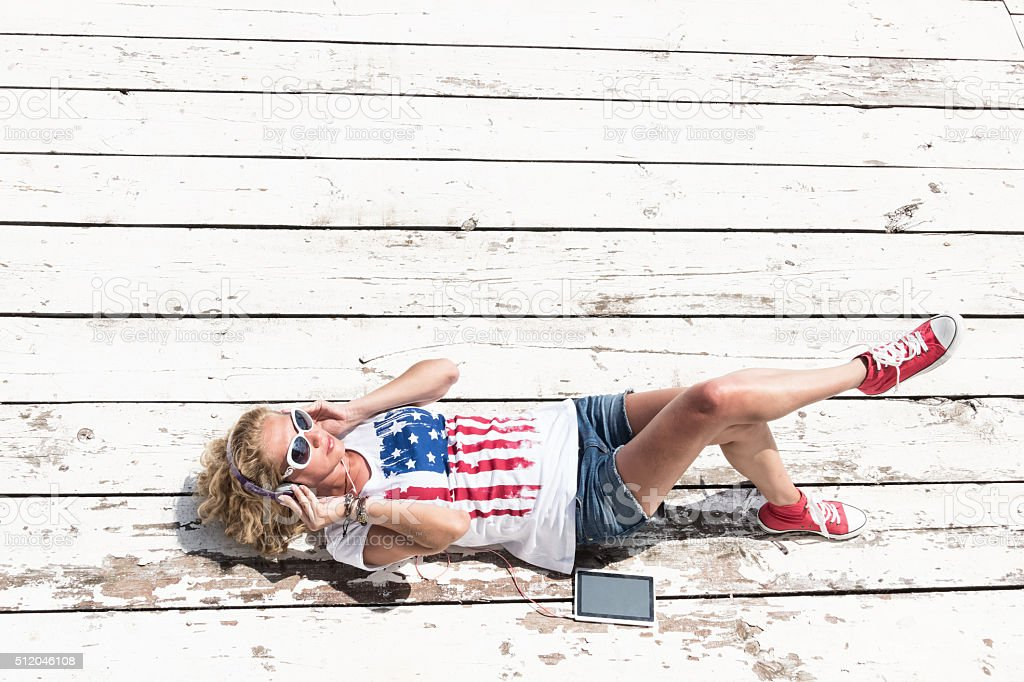 Young woman listening music on phone laying at floor stock photo