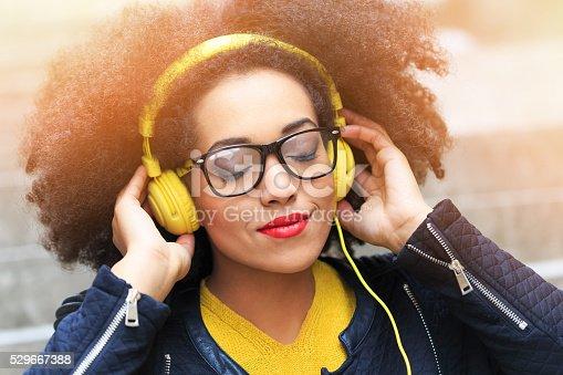 istock Young woman listening music on yellow headphones 529667388