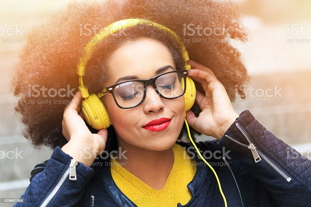 Young woman listening music on yellow headphones stock photo