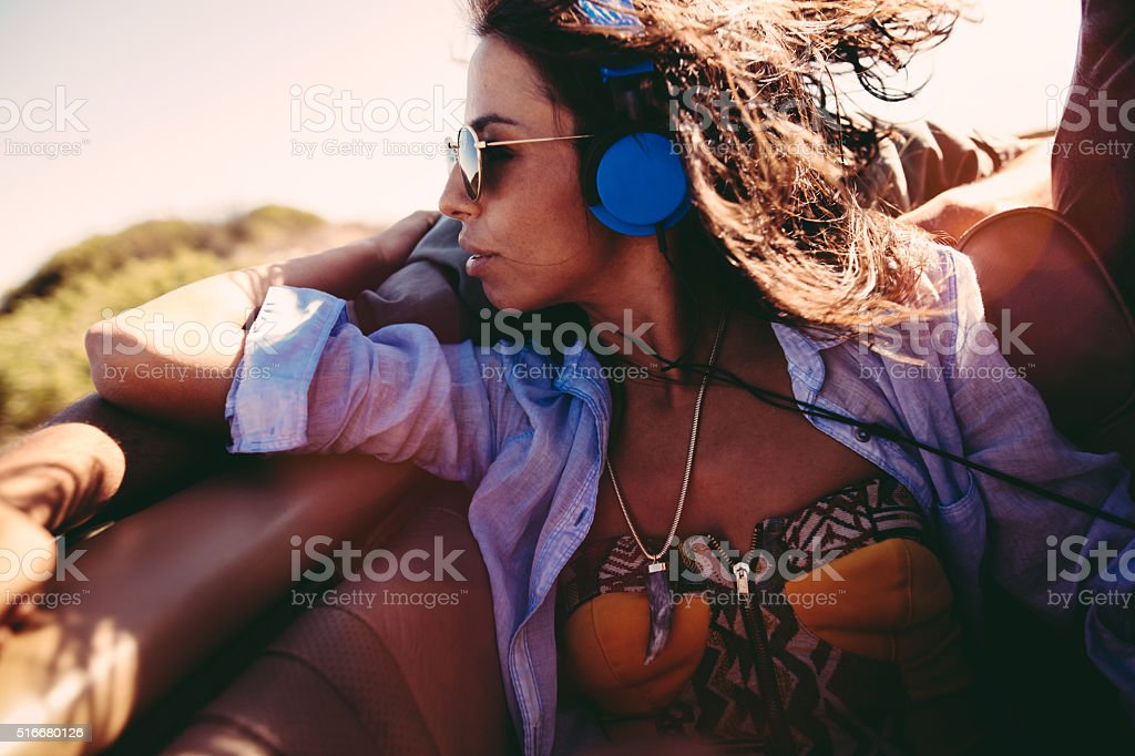 Young woman listening music with earphones during a road trip stock photo