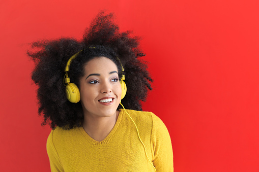 Attractive young woman with yellow headphones and blouse, listening music. On red bacground.