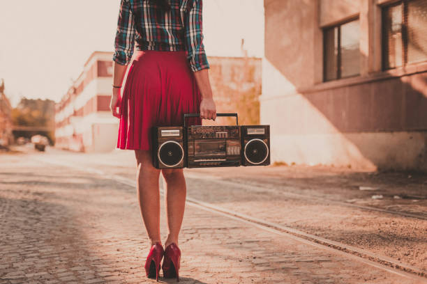 Young woman listening to boom box outdoors and enjoying a beautiful day stock photo
