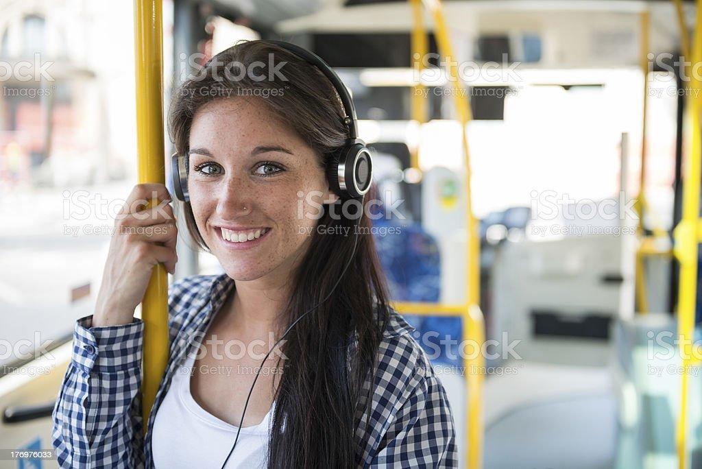 Felice giovane donna con auricolare telefono sull'autobus - foto stock
