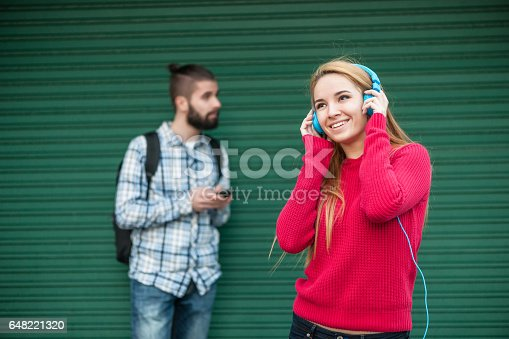 545098584 istock photo young woman listening to music, a boy behind her texting on the phone 648221320