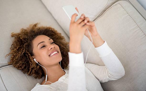 junge frau musik hören wie zu hause fühlen. - geräusche app stock-fotos und bilder