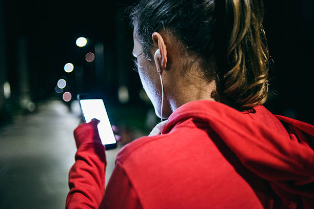 junge frau hören musik bei nacht - one song training stock-fotos und bilder