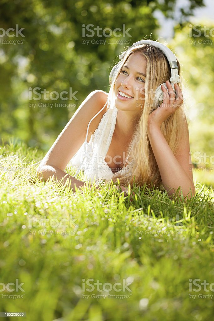 Young Woman Listening To Music In Garden royalty-free stock photo