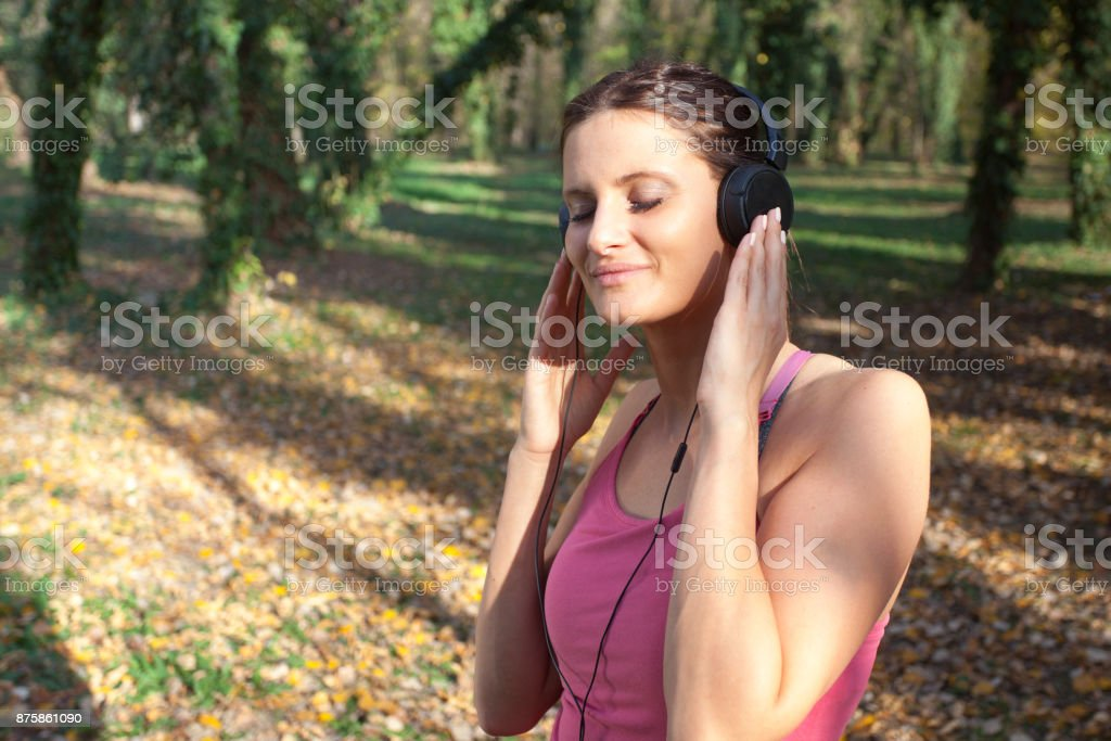 young woman listening to music in park stock photo