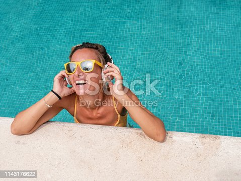 Young woman y the swimming pool listening to music on wireless headphones wile on vacation. People enjoying life
