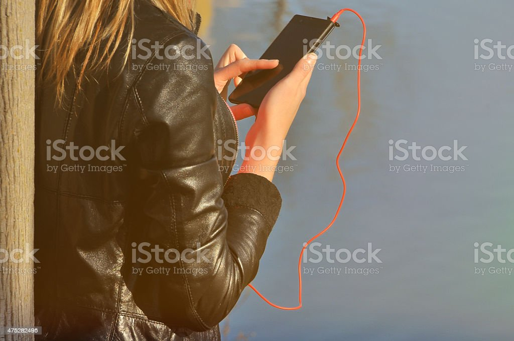Young woman listening to music on a smart phone stock photo