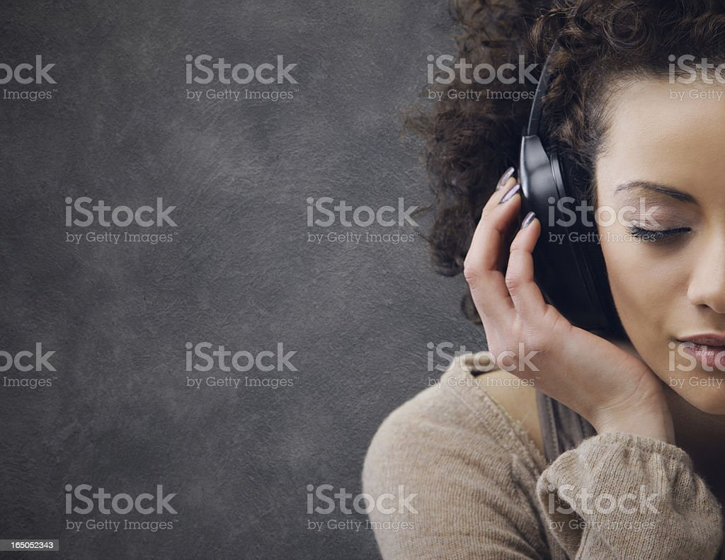 A young woman listening to music on her headphones stock photo